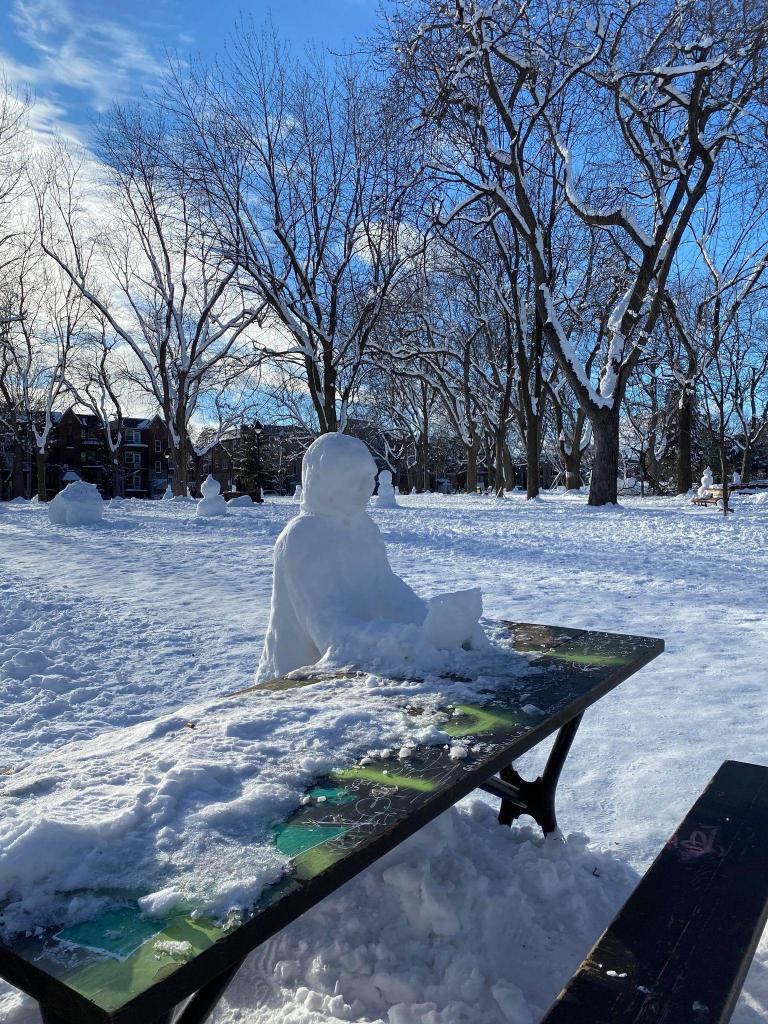 Un monsieur qui lit un livre, fait de neige, dans le Parc Sir-Wilfred-Laurier du secteur du Plateau Mont-Royal